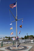 American flag and nautical flags flying at Woodcleft Esplanade in Freeport, Long Island — Stock Photo