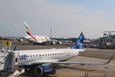 JetBlue Embraer 190 aircraft at the gate at the Terminal 5 and Emirates Airline Airbus A380 at John F Kennedy International Airport — Zdjęcie stockowe