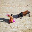 Bullfighter and black bull in action — Stock Photo #13457421