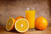 Fresh orange juice and oranges — Stock Photo