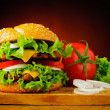 Double cheeseburger and fresh vegetables — Stock Photo