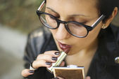 Young lady is painting her lips at the park — Stock Photo