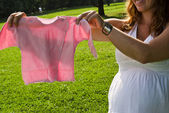 Beautiful pregnant woman is holding a baby's undershirt — Foto Stock