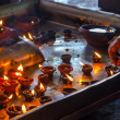 The hand lighting candles in the Indian temple - Stock Photo