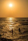 Gün batımında, iki kız denizde yüzme silhouettes — Stok fotoğraf