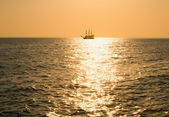 Silhouette ancient a vessel floating by sea at sunset — Stock Photo
