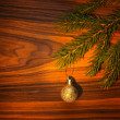 The New Year's branch of a fir-tree with a ball lies on a wooden — Stock Photo
