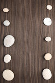 Pebbles on ebony wood texture — Stock Photo