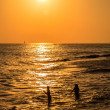 Silhouettes of two girls at sunset, swimming in the sea — Stock Photo