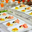 Foto Stock: Buffet table with served dish in foreground