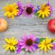 Bouquet of flowers and apples is framing on a wooden background — Stock Photo