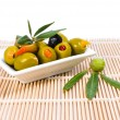 Stuffed olives with olive branch and leaves on a rustic mat — Stock Photo