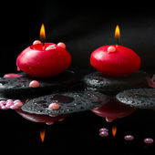 Spa concept of  red candles and pearl beads on zen stones with d — Stock Photo