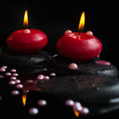 Beautiful spa concept of candles, zen stones with drops and pear — Stock Photo