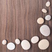 Light pebbles on wooden ebony tree background — Stock Photo