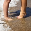 Foto Stock: Legs of kissing couple on beach