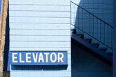 Indicazioni per sollevare su sfondo blu — Foto Stock