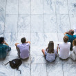 People sitting on white steps — Stock Photo