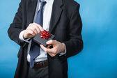 Elegant man handing a gift — Stock Photo