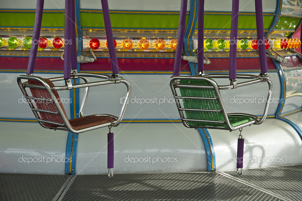 Seats of the carousel at Luna Park and the background lights  Stock Photo #12133404