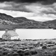 Dramatic landscape with old stone house at a lake on Isle of Mull, Scotland - Stock Photo