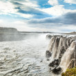 Woman standing near famous Selfoss waterfall in Vatnajokull National Park, Northeast Iceland - Stock Photo