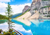 Beautiful landscape with Rocky Mountains and tourists canoeing on azure mountain lake, Alberta, Canada — Stok fotoğraf