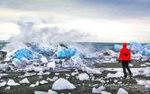 Vrouw kijken golven crash tegen ijsbergen op jokulsarlon glaciale lagune, ijsland — Stockfoto