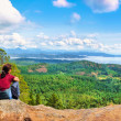 Woman sitting on a rock and enjoying the beautiful view on Vancouver Island, British Columbia, Canada — Stock Photo