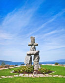 Inukshuk, symbol of the 2010 winter olympic games, with blue sky at English Bay in Vancouver, British Columbia, Canada — Stock Photo