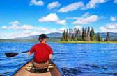 在加拿大不列颠哥伦比亚省的旷野中的湖上划独木舟的人 — 图库照片