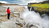 Woman standing near famous Dettifoss waterfall in Vatnajokull National Park, Iceland — Stock Photo