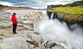 Woman standing near famous Dettifoss waterfall in Vatnajokull National Park, Iceland — Stock Photo