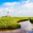 Beautiful landscape with small pond and lighthouse in the background at North Sea in Nordfriesland, Schleswig-Holstein, Germany — Stock Photo #38809257