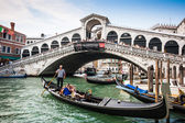 VENICE - JULY 11: Traditional gondolas and boats on Canal Grande at famous Rialto bridge on July 11, 2013 in Venice, Italy. The high traffic volume on Canal Grande is one of the city's major concerns. — Stock Photo