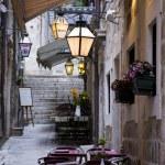 rua estreita com flores, restaurante, lâmpadas e escadas — Fotografia Stock  #10704913
