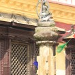 Stock Photo: Buildings, columns, Buddhstatue, prayer flags, around Swayambhunath Stupa.