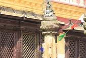 Buildings, columns, Buddha statue, prayer flags, around Swayambhunath Stupa. — Stock Photo