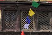 Buddhist prayer flags before wooden window. — Stock Photo