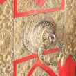 Stock Photo: Richly carved brass knob on red painted door.