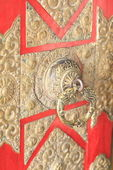 Richly carved brass knob on red painted door. — Stock Photo