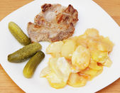 Fried steak, potato and pickles. — Stock Photo