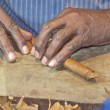 Cigar maker puts the finishing touches on a Cuban cigar. — Stock Photo #21260979