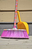 Colourful broom and dustpan — Stock Photo