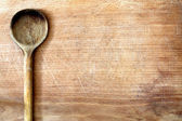 Old grunge wooden cutting kitchen desk board with spoon — Stock Photo