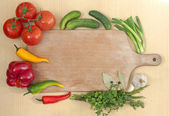 Vegetables and spices border and empty cutting board — Stock Photo