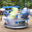 Carousel in motion and happy kids on playground — Stock Photo