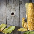 Autumn leaves on wooden boards with corn background — Stock Photo