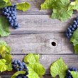 Foto Stock: Grapes with green leaves on vintage wooden boards background