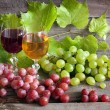 Royalty-Free Stock Photo: Glass of wine and grapes on old wooden boards